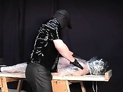 Latex fetish slave takes some brutal treatment from a dominating guy