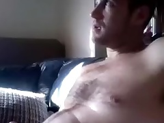 Dishy guy is having fun at home and filming yourself on computer webcam
