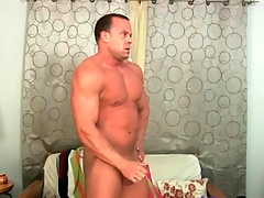 Smooth muscular guy masturbates onto his stomach