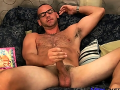 Hot bear to glasses plays with his cock while leafing through a gay porn mag
