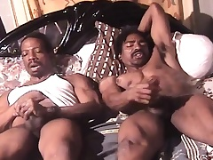 Muscled black guys lie side by side on the bed plus masturbate together