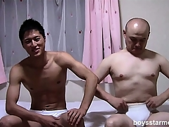 Two Asian guys take each other's clothes off and sit on the adjoin stroking their cocks