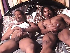 Two sexy and blistering dark skinned studs masturbate together unaffected by the bed